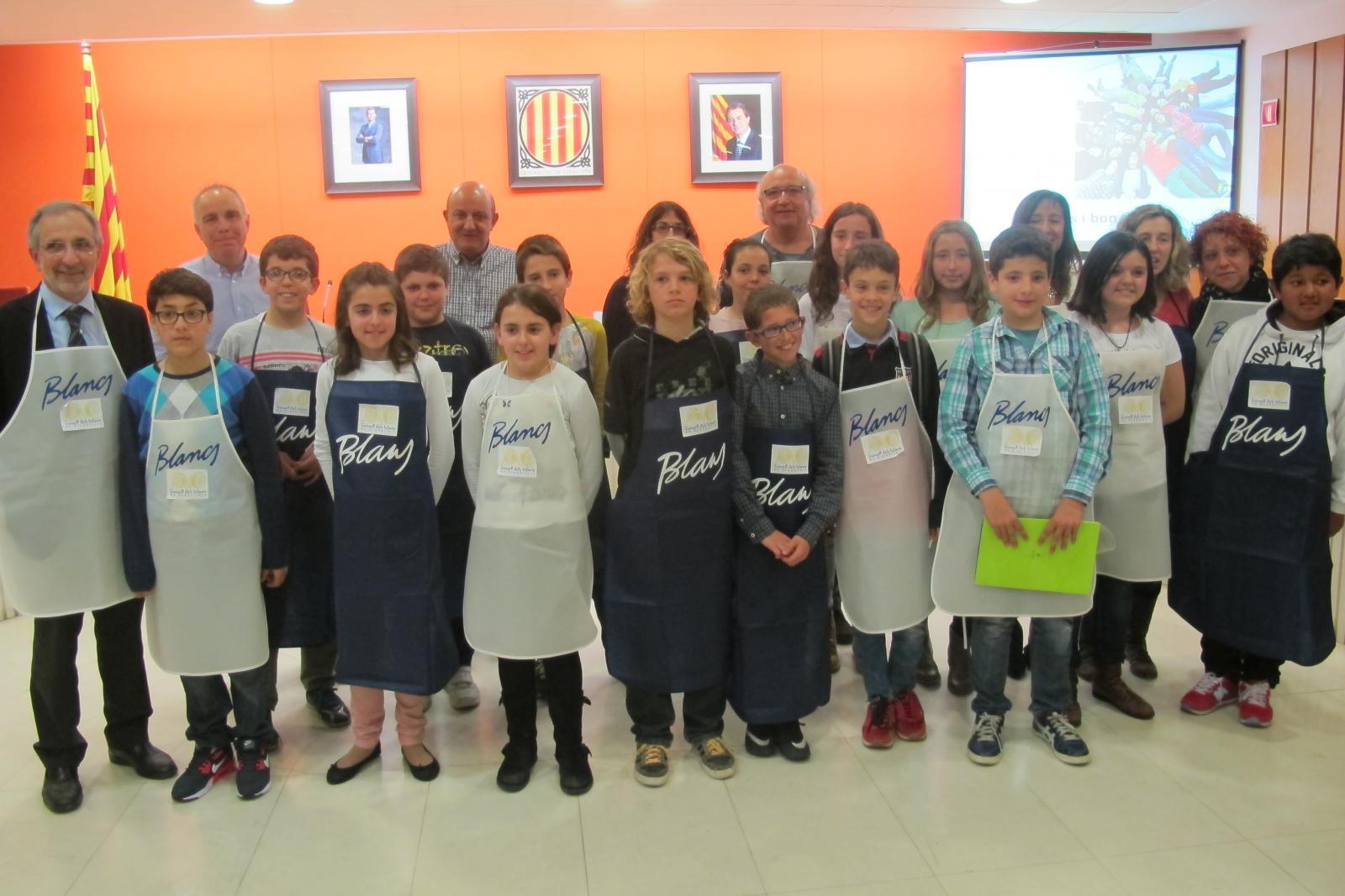 El Consell dels Infants vestits amb davantal de les colles de Blancs i Blaus perquè van fer la seva exposició sobre la Festa Major com a cuiners de la festa